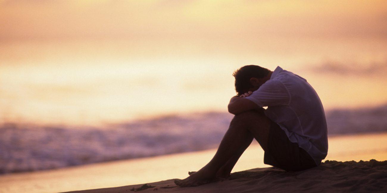 Man hugging knees on beach at sunset